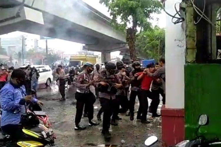 Salah seorang massa aksi saat diamankan polisi usai bentrok di depan kantor KPU Sulsel, Kamis (26/11/2020).