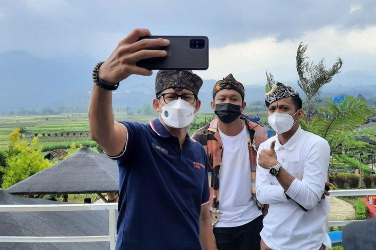 Menteri Pariwisata dan Ekonomi Kreatif Sandiaga Salahudin Uno saat berfoto selfie bersama Denny Cak Nan dan Cak Percil di Desa Wisata Pujon Kidul, Kabupaten Malang, Sabtu (22/5/2021).