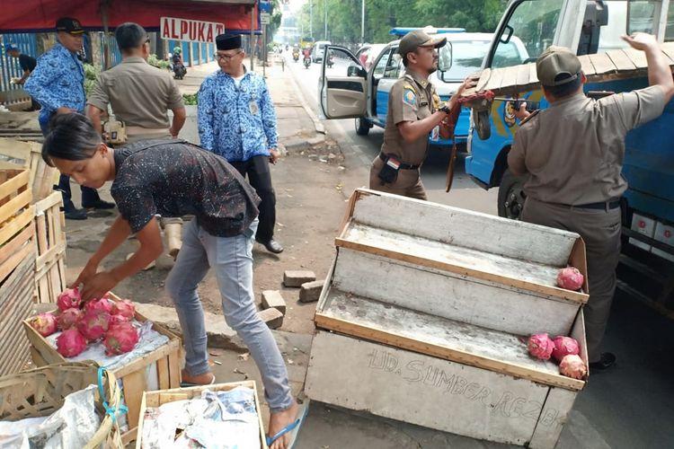 Petugas Satpol PP Jakarta Timur saat menertibkan sejumlah Pedagang Kaki Lima (PKL) yang keberadaannya kerap mengganggu arus lalu lintas di Jalan Raya Bogor, Jakarta Timur, Senin (28/10/2019).