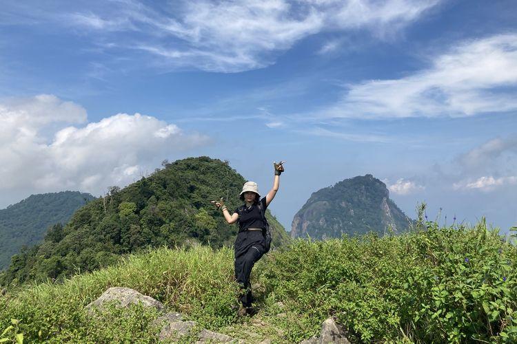 Seorang pendaki dengan pemandangan puncak Camp Area Gunung Parang yang terlihat dari jalur pendakian Gunung Parang via Pesanggrahan di Kabupaten Purwakarta, Jawa Barat, Minggu (13/6/2021).