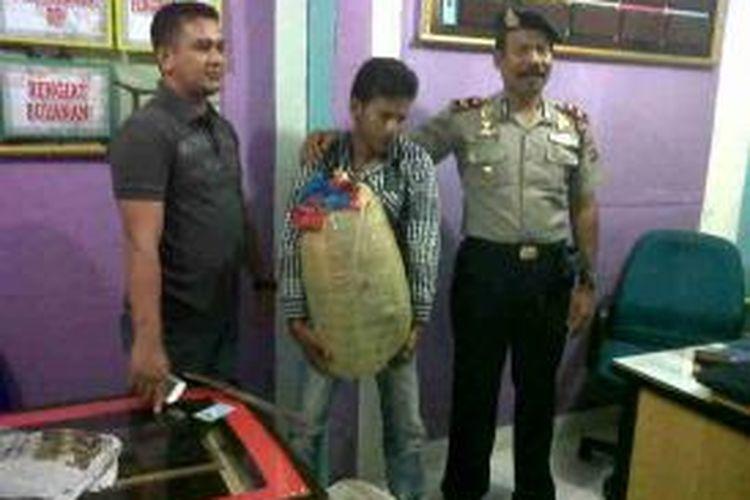 Kapolsek Peusangan Ipda Syarifuddin dan Kanitreskrim mengapit pelaku Bahagia bersama barang bukti 10 kg ganja. Sabtu (20/7) di Mapolsek Peusangan. (DESI)
