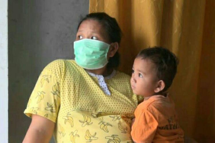 Nurazmi (26), sedang hamil delapan bulan memangku anaknya, Azam, terpapar kabut asap karhutla di Desa Rimbo Panjang, Kecamatan Tambang, Kabupaten Kampar, Riau, Jumat (20/9/2019).