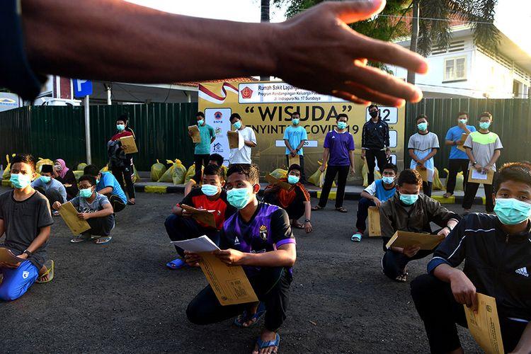 Sejumlah santri asal Ponpes Gontor mendengarkan penjelasan petugas ketika mengikuti wisuda penyintas  COVID-19 di halaman Rumah Sakit Lapangan Surabaya, Jawa Timur, Selasa (28/7/2020). Berdasarkan data Satgas penanganan COVID-19 menyatakan jumlah pasien sembuh di Jawa Timur pada (28/7) sebanyak 401 pasien sehingga total pasien yang dinyatakan sembuh tercatat 13.081 orang.