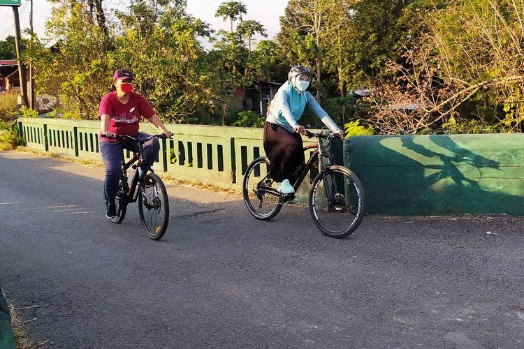 Dua pesepeda tetap mengenakan masker saat bersepeda dalam masa pandemi Covid-19.