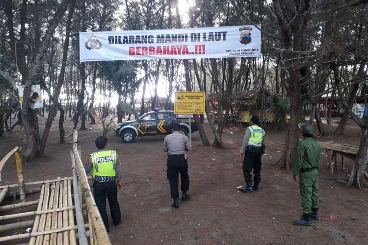 Spanduk larangan mandi di laut dipasangan anggota polisi di sepanjang pantai di Kabupaten Kebumen, Jawa Tengah.