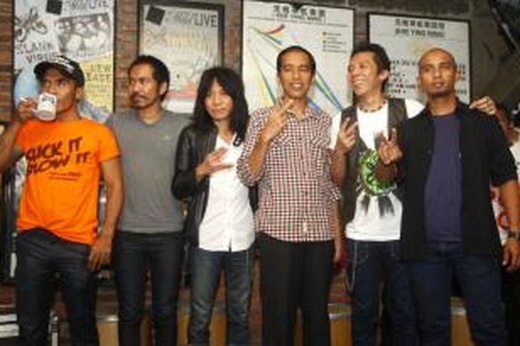 Para personel Slank, yaitu Kaka (kiri), Ridho Hafiedz (kedua dari kiri), Abdee Negara (ketiga dari kiri), Bimbim (kedua dari kanan), dan Ivanka (kanan), berpose bersama bakal calon presiden Joko Widodo atau Jokowi di markas Slank, Gang Potlot III, Kalibata, Jakarta Selatan, Selasa (27/5/2014).  Dalam pertemuan itu Slank memberi usulan nama-nama yang layak duduk dalam pemerintahan jika Jokowi terpilih menjadi presiden.