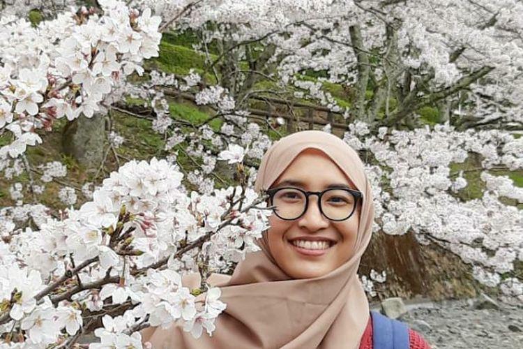 Aprilia Maharani (27) berfoto bersama sakura di Kyoto, Jepang.