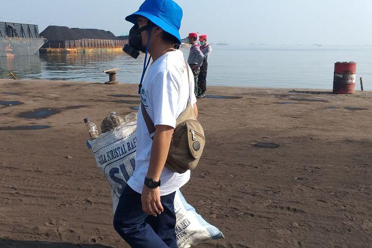Seorang peserta Bersih Laut dan Pantai membawa karung berisi sampah yang dikumpulkan dari kawasan Pelabuhan Karya Citra Nusantara (KCN) Marunda, Jakarta Utara, Kamis (12/9/2019).