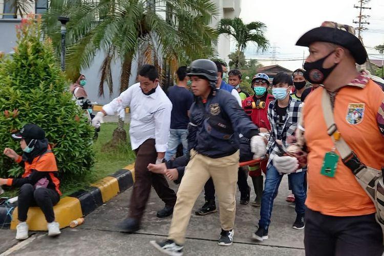 Tim medis sedang mengevakusi para demonstran yang pingsan saat aksi penolakan UU Cipta Kerja di Samarinda, Kaltim, Senin (12/10/2020).