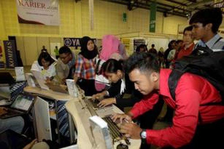 Ilustrasi: Pencari kerja mengisi lamaran di salah satu stan perusahaan di Kompas Karier Fair di Balai Kartini, Jakarta.