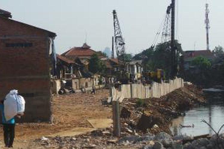 Alat berat sedang bekerja di lahan bekas pemukiman Kampung Pulo yang digusur di pinggiran Sungai Ciliwung. Senin (31/8/2015).