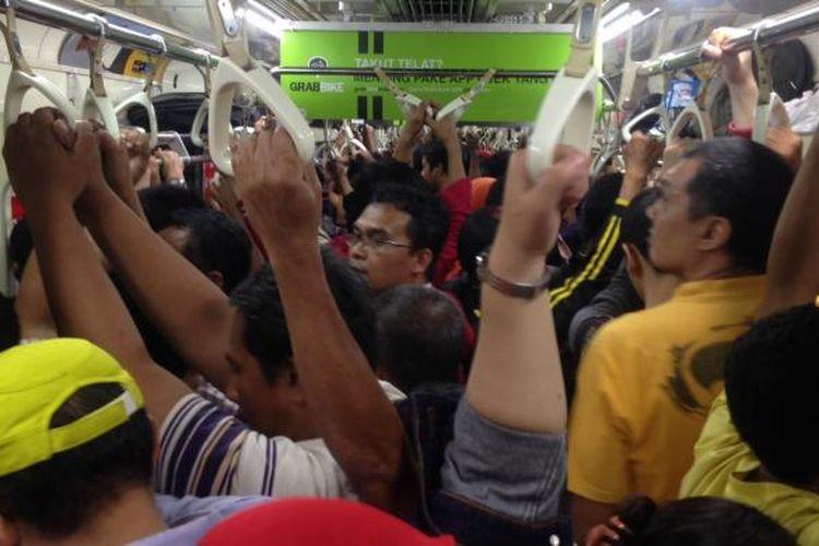 Suasana Kereta Rel Listrik (KRL) Commuter Line Jabodetabek saat jam-jam sibuk pada hari kerja.