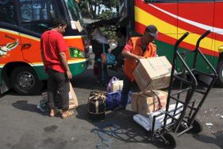 Penjual jasa porter, Wawan, menata barang bawaan warga yang turun dari bus di Terminal Kalideres, Jakarta Barat, Minggu (26/8). Arus mudik dan balik menjadi berkah bagi mereka untuk menambah penghasilan.