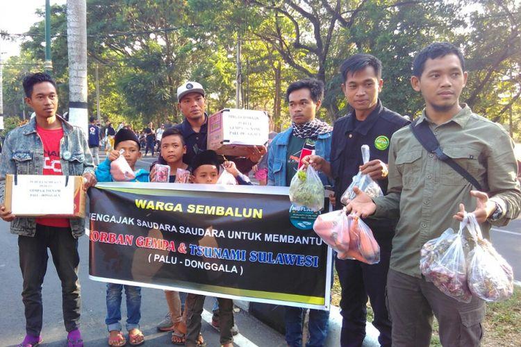 Warga Sembalun, korban gempa Lombok, menggalang dana dan membagikan stroberi gratis ke pengunjung CFD Mataram, Minggu (7/10/2018).