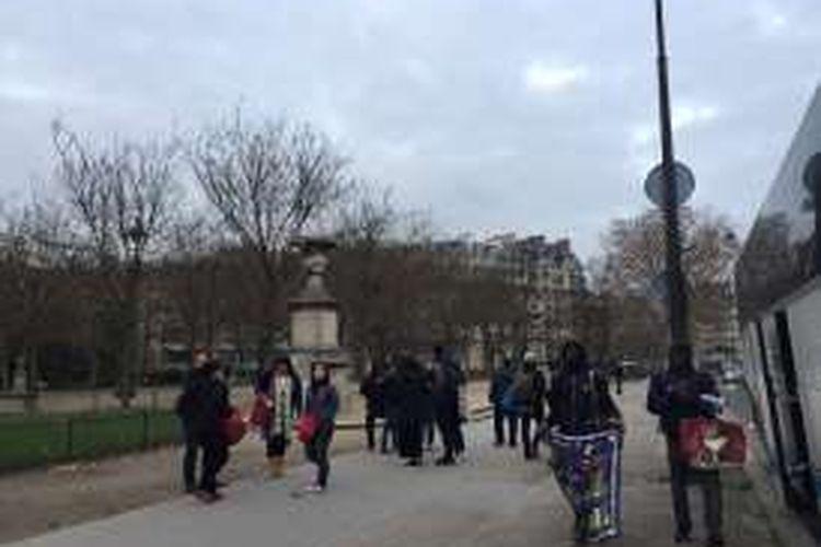 Pengasong suvenir di Menara Eiffel (kanan), Paris, Perancis, menawarkan barang dagangan dengan bahasa masing-masing turis, Minggu (27/11/2016).