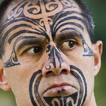 Seorang pria Maori dengan tato di wajahnya.