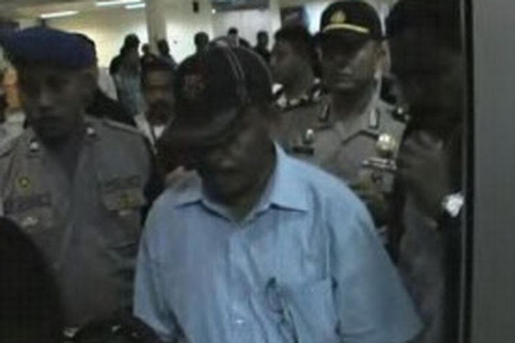 Wakil Bupati Aru, Umar Djambumona, mengenakan kemeja putih dan topi hitam saat digiring sejumlah polisi di Bandara Internasional Pattimura Ambon, Jumat (21/6/2013)
