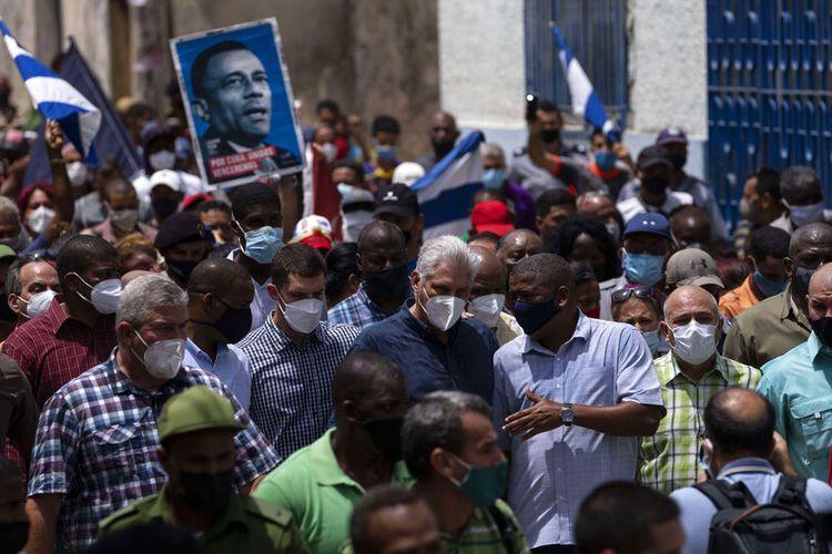 Presiden Kuba Miguel Diaz Canel (tengah) berjalan bersama para pengikutnya setelah protes anti-pemerintah di San Antonio de los Banos, Kuba, Minggu 11 Juli 2021.