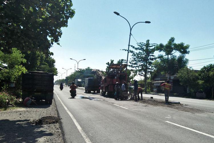 Salah satu ruas jalan raya di jalur pantura dekat perbatasan Gresik-Lamongan, terlihat terus diperbaiki oleh petugas.
