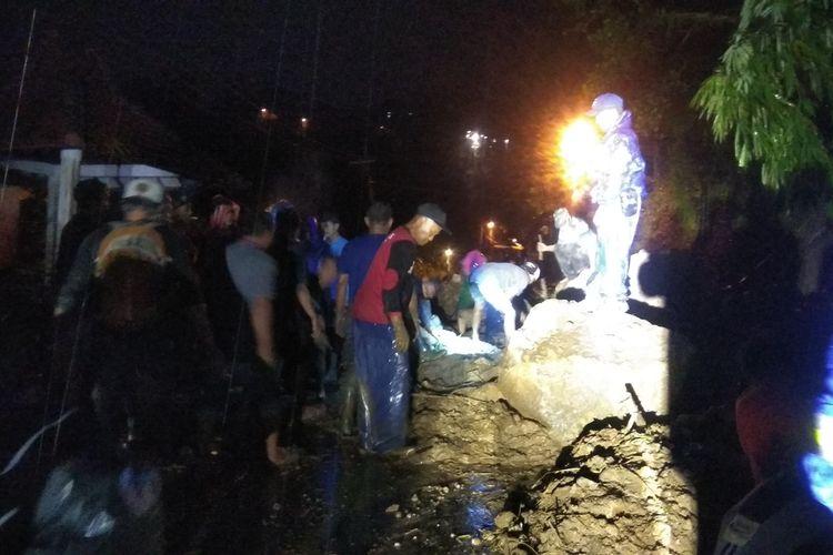 Pembersihan material longsor yang menutup badan jalan di jalur penghubung Pacet - Trawas, Kabupaten Mojokerto, Jawa Timur, dilakukan petugas dengan bantuan alat berat, Jumat (7/2/2020) malam.