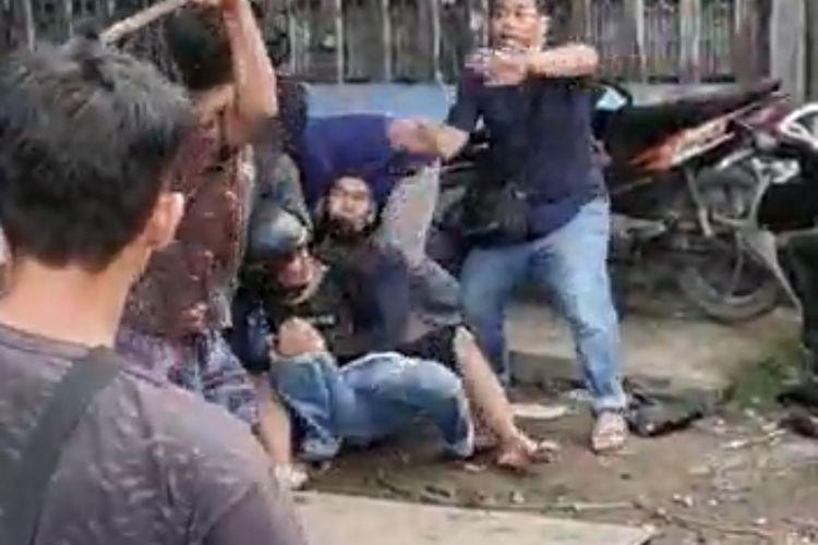 Tangkapan layar pelaku menjadi bulan-bulanan warga saat anggota polisi berusaha mengamankannya.