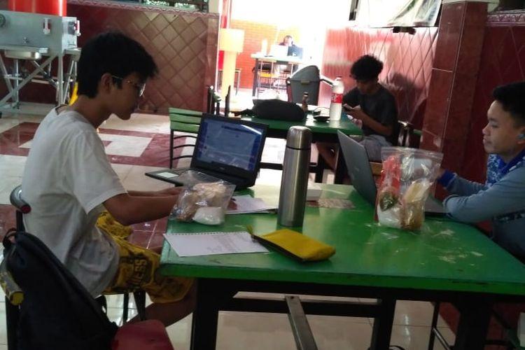 Dua mahasiswa penghuni Asrama Universitas Indonesia menerima paket nasi bungkus di hari-hari mereka kesulitan mencari makanan, seiring merosotnya jumlah warung di sekitar kampus akibat pandemi Covid-19.