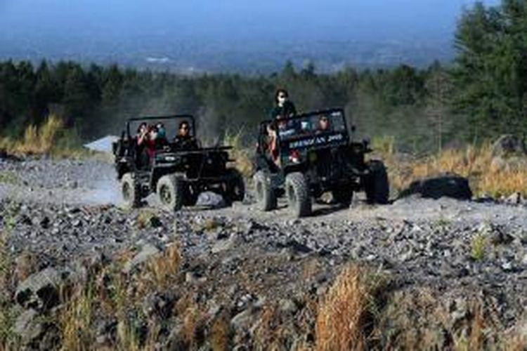 Para pelancong menggunakan mobil jeep menelusuri lereng-lereng Gunung Api Merapi, Yogyakarta menyaksikan bekas dampak erupsi hebat yang terjadi pada 2010.