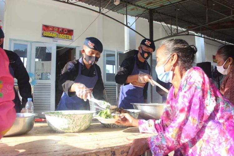 Anggota Brimop Polda Jateng membagikan makanan prasmanan kepada para pengungsi Merapi di Desa Banyurojo, Kecamatan Mertoyudan, Kabupaten Magelang, Jumat (20/11/2020),