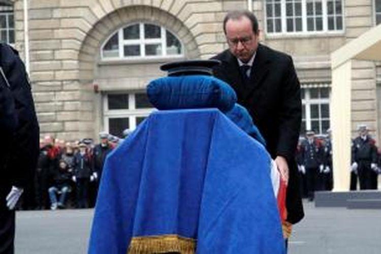 Presiden Perancis Francois Hollande memberikan penghormatan terakhir di hadapan peti jenazah Ahmed Marabet (40), seorang polisi yang tewas dalam serangan terhadap majalah Charlie Hebdo. Dalam rangkaian serangan maut di Paris pekan lalu, sebanyak tiga orang polisi tewas.