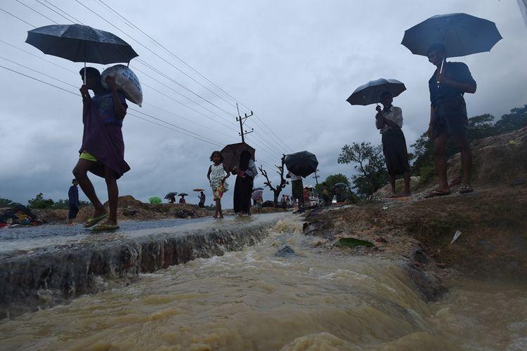Foto yang diambil pada September 2017 menunjukkan warga Rohingya yang berjalan di bawah guyuran hujan di kamp pengungsian di Kutupalong, Bangladesh.
