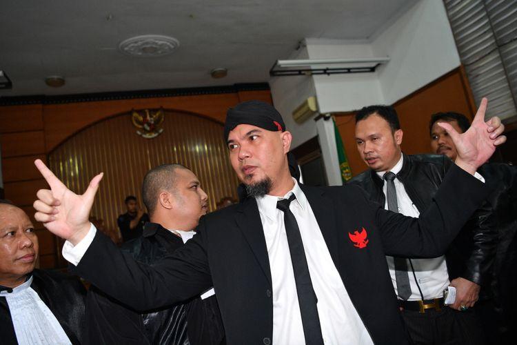 Terpidana kasus ujaran kebencian Ahmad Dhani (tengah) mengacungkan kedua tangan seusai menjalani sidang putusan di Pengadilan Negeri Jakarta Selatan, Jakarta, Senin (28/1/2019). Majelis hakim memvonis Ahmad Dhani dengan hukuman satu tahun enam bulan penjara, dan atas putusan hakim tersebut kejaksaan langsung menahan terpidana. ANTARA FOTO/Sigid Kurniawan/ama.