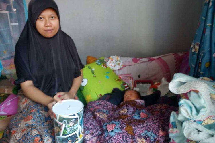 Riska (27) bersama bayinya, yang baru berumur sepekan di rumahnya di Desa Rahong, Cianjur, Jawa Barat, Jumat (17/01/2020). Riska membayar biaya persalinan anak pertamanya itu menggunakan uang koin pecahan Rp1.000