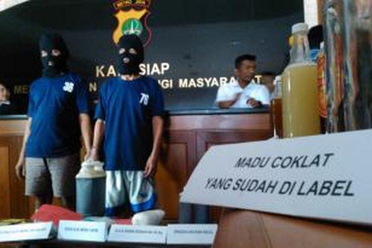 Dua lansia, Jahuri (55) dan Suhatma (70), diamankan aparat Polres Metro Jakarta Timur karena diduga mengoplos madu palsu, Kamis (11/6/2015).
