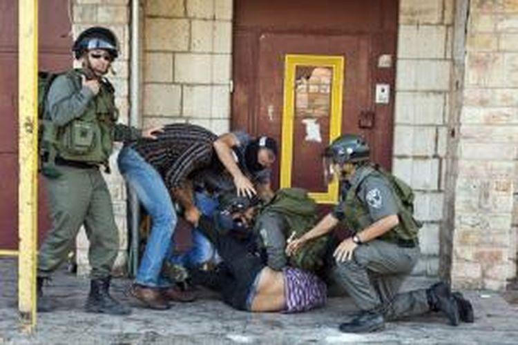 Polisi Israel menangkap seorang pemuda Palestina di salah satu sudut kota Jerusalem, Jumat (27/6/2013), usai ibadah shalat Jumat. Polisi menahan setidaknya sembilan pemuda yang melempari polisi dengan batu di luar wilayah kota tua.