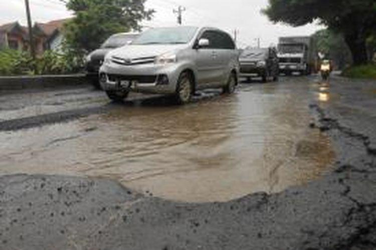 Para pengendara kendaraan bermotor berusaha menghindari jalan yang berlubang  di jalan Pantura , tepatnya di Desa Katonsari Demak, Jawa Tengah. Gambar diambil pada Senin (3/2/2014)