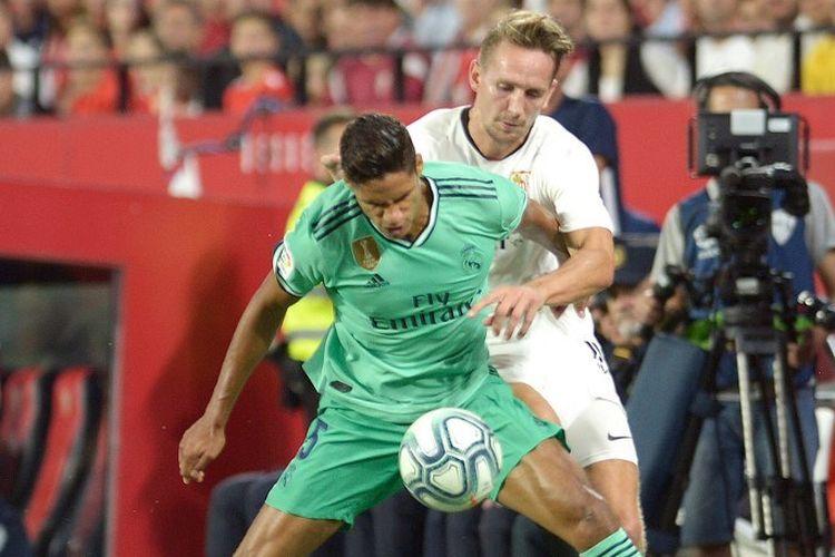 Luuk de Jong (belakang) dan Raphael Varane berebutan bola pada pertandingan Sevilla vs Real Madrid dalam lanjutan La Liga Spanyol di Stadion Ramon Sanchez Pizjuan, 22 September 2019.
