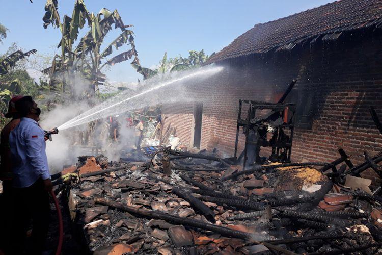 Petugas saat melakukan proses pemadaman api di dua rumah di Desa Banyu Urip, Kecamatan Kedamean, Gresik, Rabu (4/8/2021).