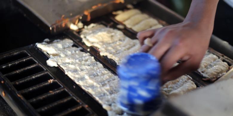 Maulana, menyiapkan kue pancong untuk para pembeli di Pasar Pusong, Kecamatan Banda Sakti, Kota Lhokseumawe, Aceh, Sabtu (21/1/2017).