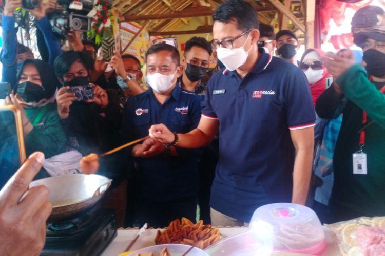 Menteri Parekraf Sandiaga Uno mencoba menggoreng Burayot, makanan khas Garut saat mengunjungi Desa Wisata Cangkuang, Minggu (22/08/2021)