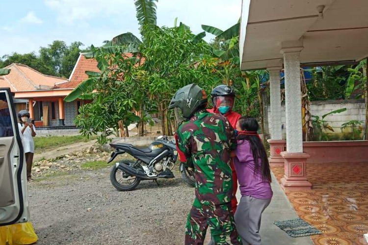 Kapolsek Karangrayung, AKP Lamsir (APD merah) dan seorang anggota TNI jemput paksa satu keluarga reaktif rapid test di Desa Sumberjosari, Kecamatan Karangrayung, Kabupaten Grobogan, Jawa Tengah,Kamis (30/4/2020) siang