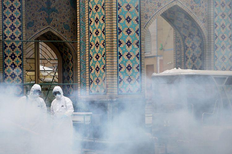 Anggota tim medis menyemprotkan disinfektan untuk membersihkan tempat di luar tempat suci Imam Reza, setelah wabah coronavirus, di Mashhad, Iran.
