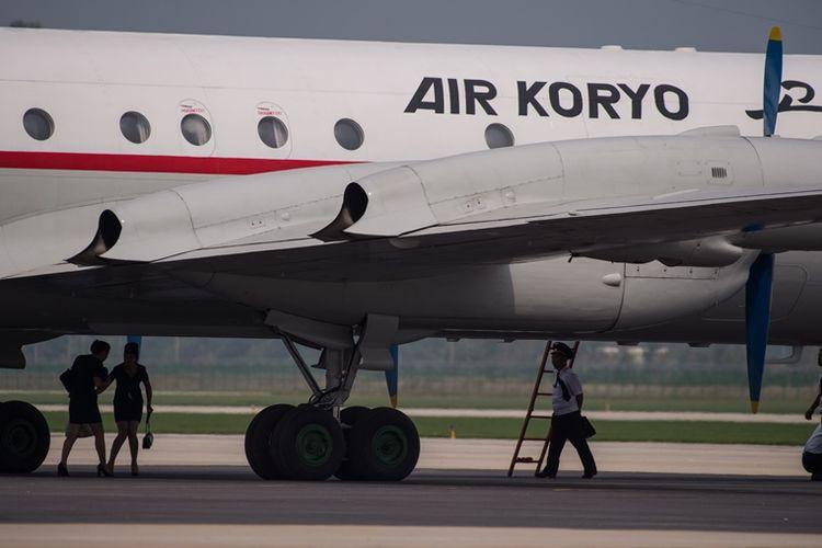 Kru maskapai udara Korea Utara Air Koryo berjalan di bawah pesawat yang terparkir di Wonsan.