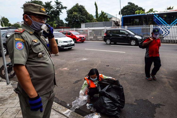 Seorang warga memngambil sampah di trotoar jalan karena tidak menggunakan masker saat patroli penegakan aturan pembatasan sosial berskala besar (PSBB) di Jl. Matraman Raya, Kecamatan Jatinegara, Jakarta Timur, Selasa (19/5/2020). Dalam kegiatan patroli PSBB tersebut, target penegakan untuk masyarakat yang tidak mengunakan masker dijalanan.