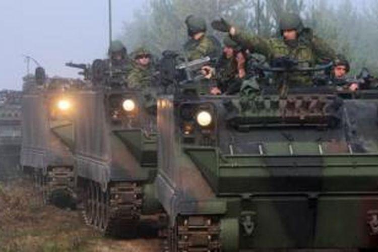 Para prajurit naik di atas tank dalam latihan militer bersama antara Lituania, Polandia dan Ukraina pada September 2012 di Pabrade, dekat Vinius, Lithuania.