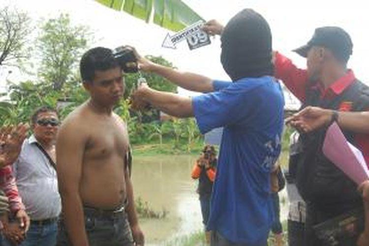 Budi Santosa (24) warga Domenggalan RT 08 RW 03, Kecamatan Demak Kota mempraktekan cara menghabisi nyawa adik kandungnya sendiri Heri Laksono (19)yang diperankan oleh petugas, dalam rekonstrusi, Jumat (8/11/20013)