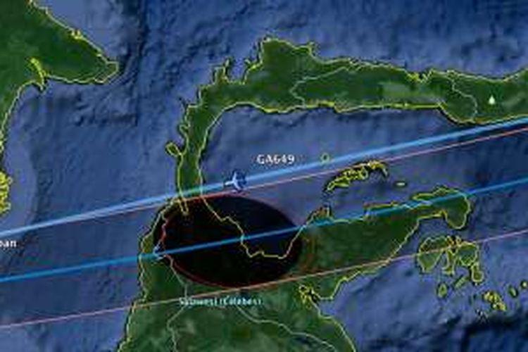 Lintasan gerhana matahari total (bulatan hitam) dan rute Garuda Indonesia GA649 yang bersinggungan.