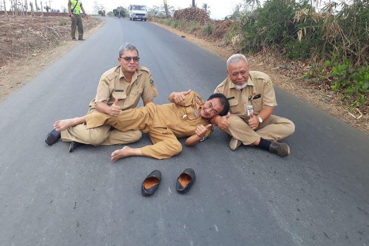 Bupati Banjarnegara Budhi Sarwono (tengah) tiduran di ruas jalan Kutawuluh - Gumiwang, Kabupaten Banjarnegara, Jawa Tengah, Senin (21/10/2019).