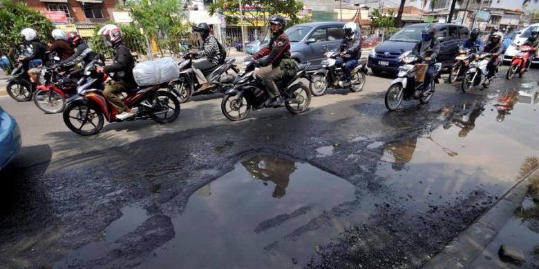 Pengendara motor menghindari kubangan air karena rusaknya aspal di Jalan Gunung Saharai, Jakarta, Senin (1/4/2013). Lubang di jalan yang tertutup genangan air sering membuat pengendara motor terperosok dan jatuh.