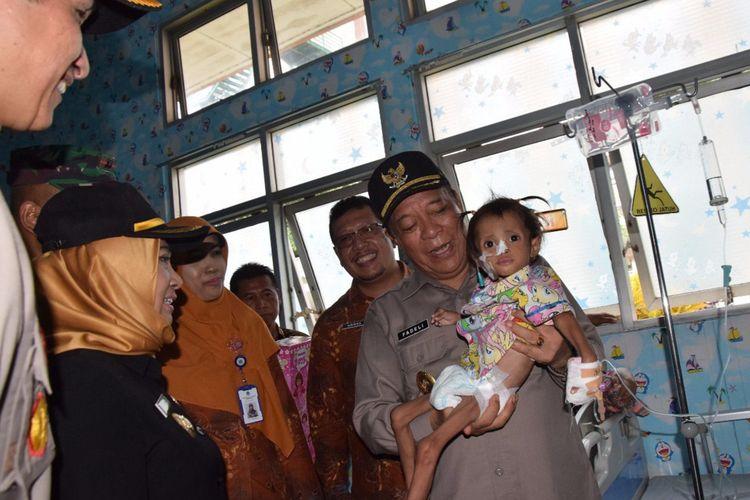 Bupati Lamongan Fadeli, saat menggendong Meilani Alfira Damayanti yang sedang menjalani perawatan di RSUD dr Soegiri Lamongan.