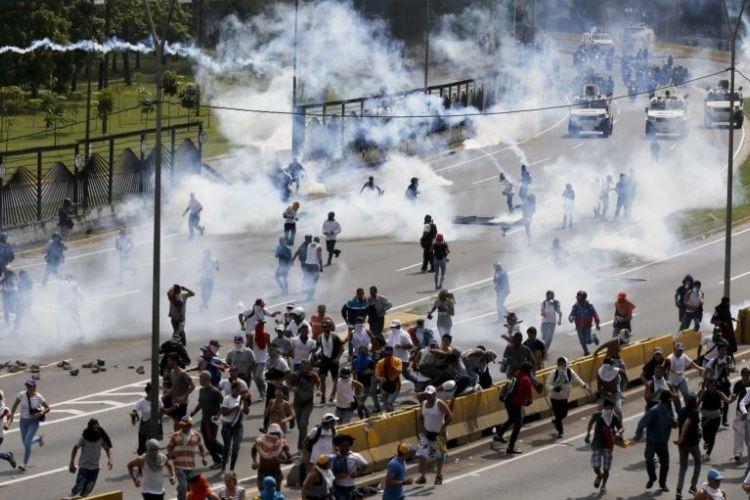 Pasukan keamanan menembakkan gas air mata ke arah demonstran anti-pemerintah di Caracas, Venezuela, Rabu (19/4/2017). Awalnya unjuk rasa damai, lalu rusuh sehingga tiga orang tewas hari itu.